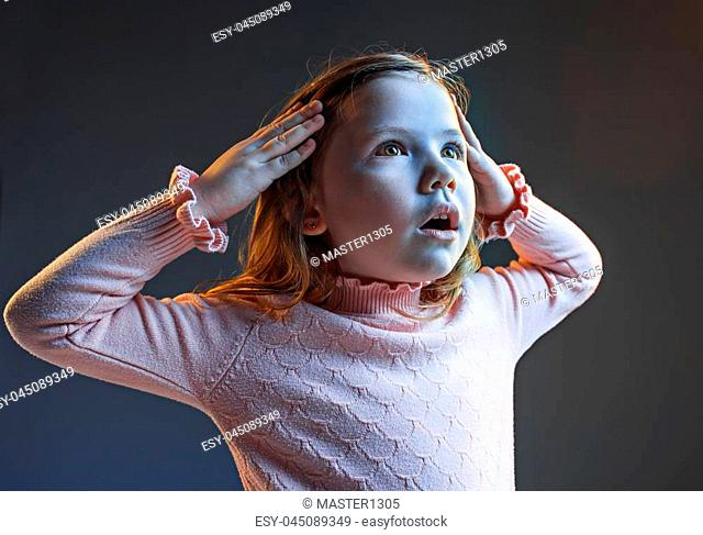 The anger and surprised teen girl. Hate, rage. Crying emotional angry teenager in colorful bright lights at studio background. Emotional face