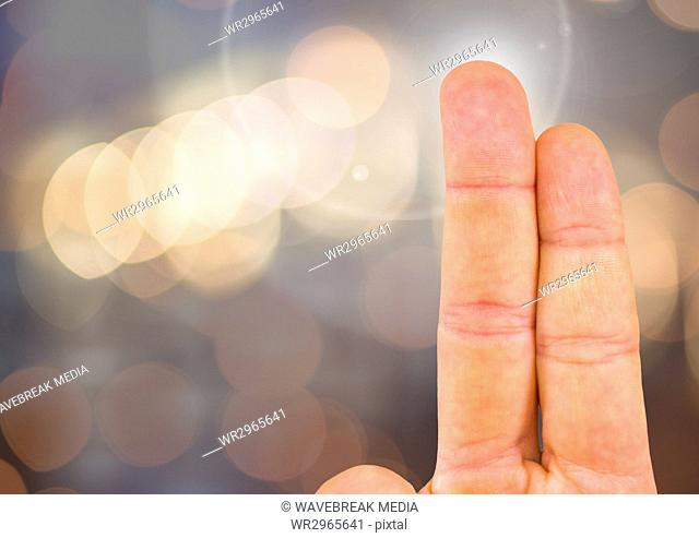Two fingers with sparkling light bokeh background
