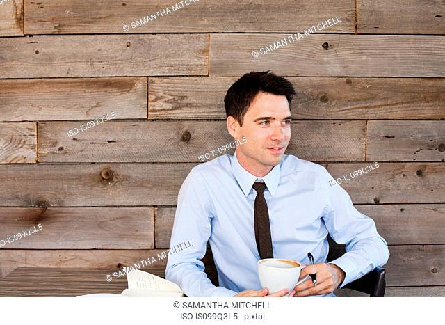 Businessman in cafe with coffee, portrait