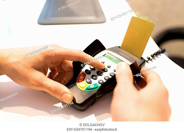 finance, technology, payment , money and people concept - close up of hand entering pin code to bank terminal with credit car