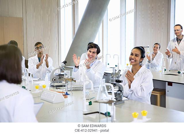 College students clapping for classmate in science laboratory classroom