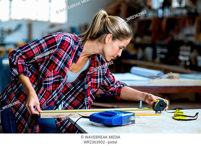 Female carpenter measuring length of wooden plank