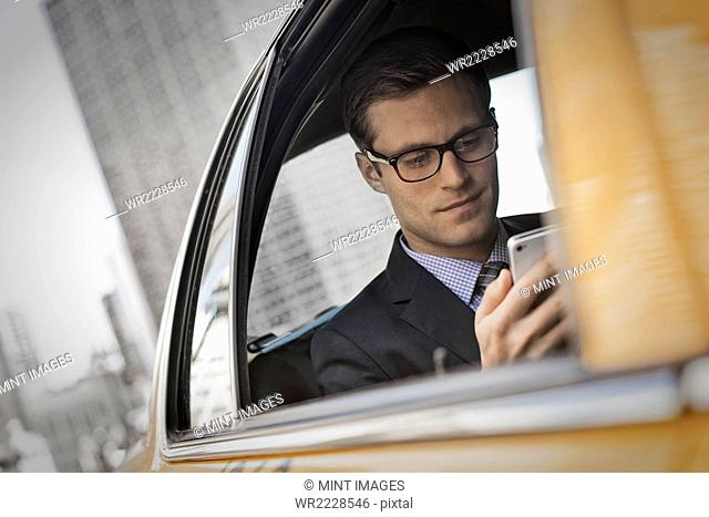 A working day. Businessman in a work suit sitting in a cab checking his phone