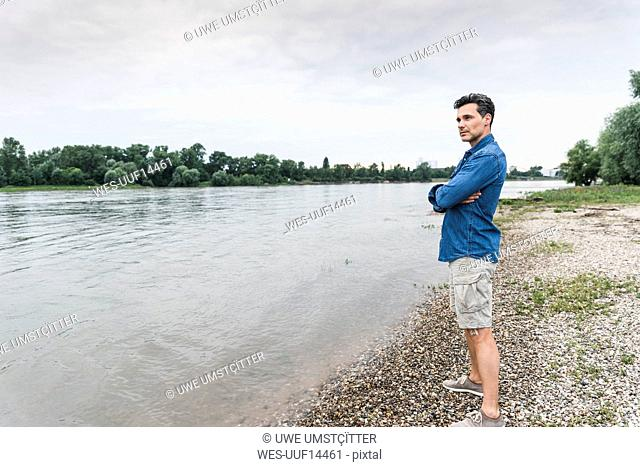 Man standing at the riverside looking out