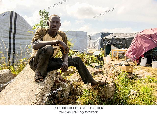 The Jungle, Calais, France. The Darfur, Sudan born Ali, sitting on pieces of demolished concrete in front of his improvised shed inside the refugee camp