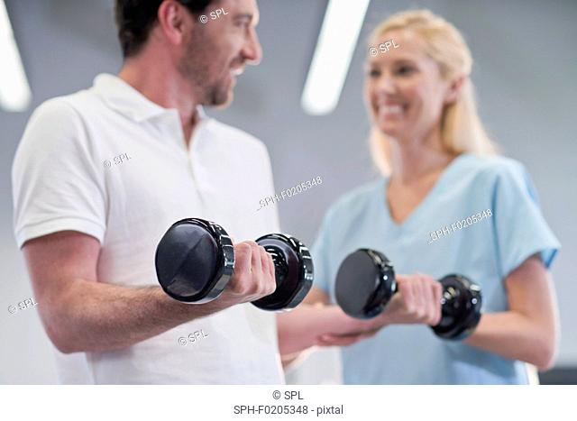 Nurse showing man how to use hand weights