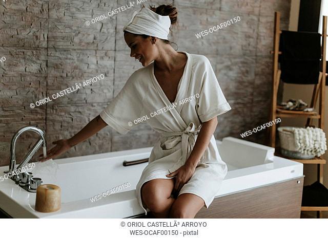 Young woman preparing a bath in a spa