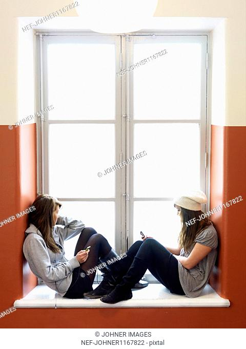 Two girls sitting on sill