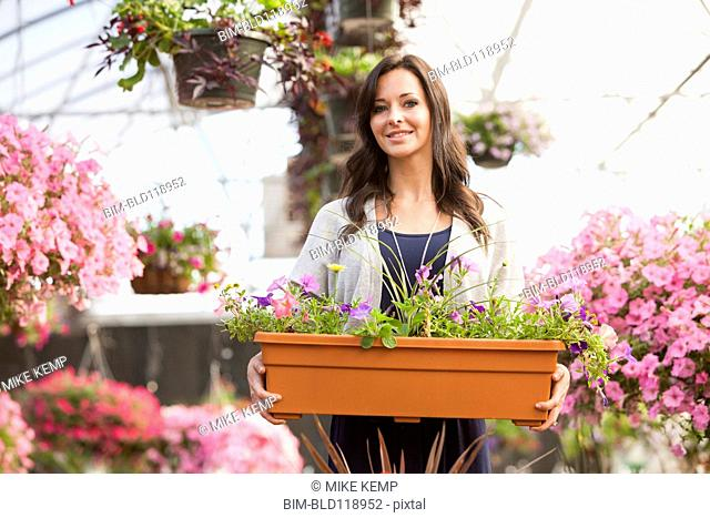 Caucasian woman carrying potted flowers in plant nursery