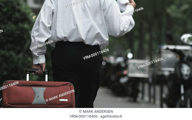 businessman walking down a city street in Europe dragging a suitcase and looking at a map