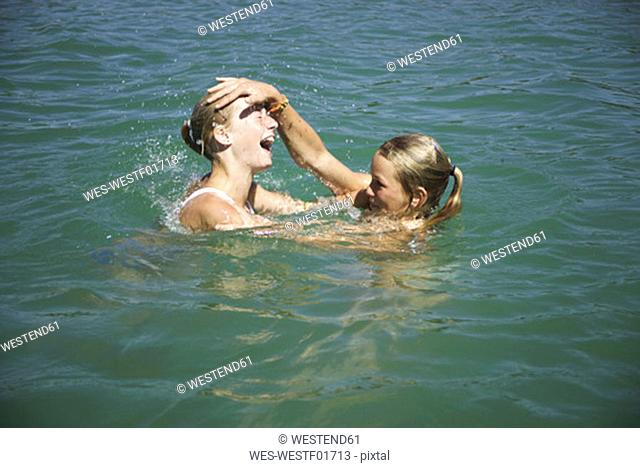 Teenage girls (13-15) playing in water, side view