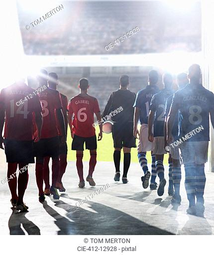 Silhouette of soccer players walking to field