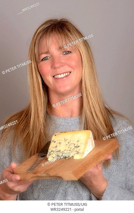 Woman holding a cheese board and a slice of blue cheese