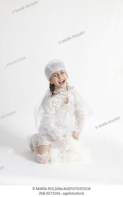 happy little girl wearing bubble wrap