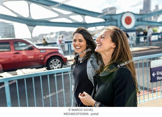 UK, London, two happy women walking on the Tower Bridge