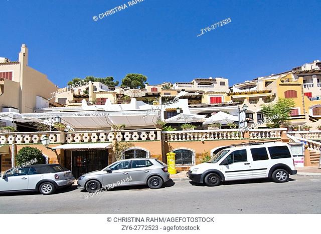 Charming architecture and parked cars on a sunny day in Cala Fornells, Mallorca