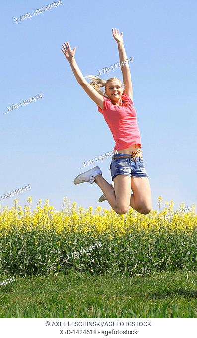 young blonde woman enjoying a walk in spring landscape jumping in the air