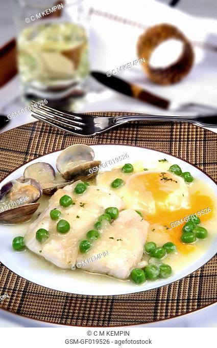 Hake in parsley sauce with clams, peas, and poached egg