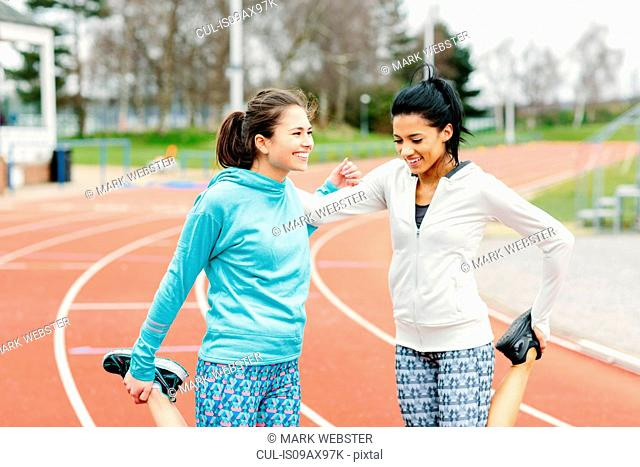 Two young women on running track, exercising, stretching