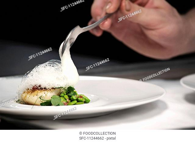 Chef plating up fish and broad bean dish during service at working restaurant