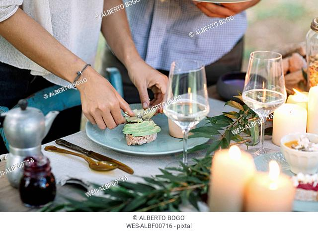 Close-up of couple preparing a romantic candlelight meal outdoors