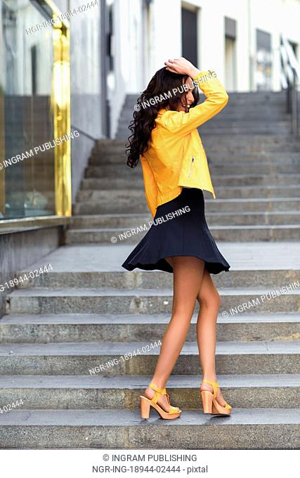 Young brunette woman, model of fashion, wearing orange modern jacket and blue skirt dancing in stairs. Pretty caucasian girl with long wavy hairstyle