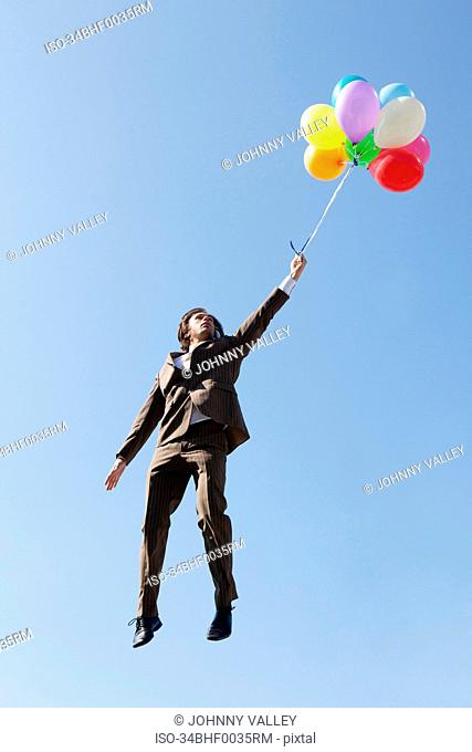 Businessman floating with balloons