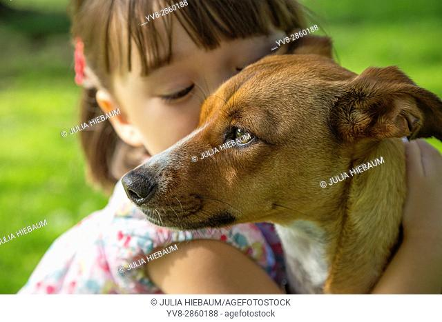 Toddler girl hugging her dog in the park, San Diego, California