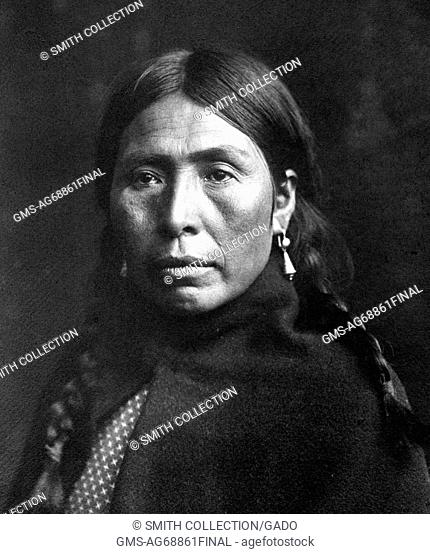 Portrait of a Native American woman, her hair braided, dark blanket over her shoulders, titled 'Vancouver Island Type, A representative face of the people...