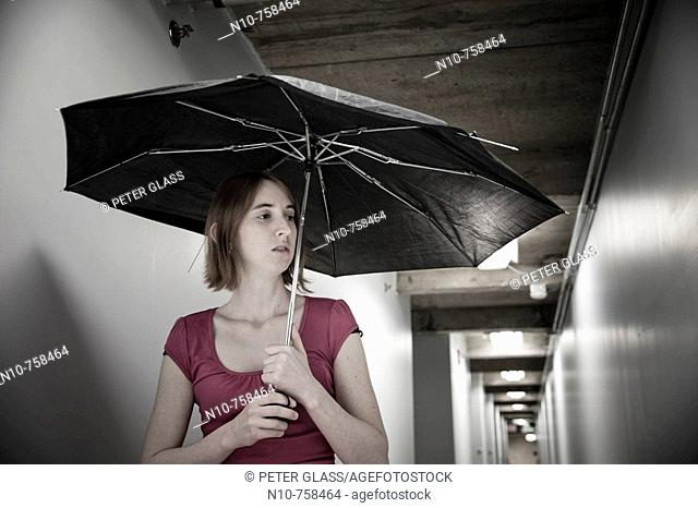 Young woman, holding a broken umbrella, standing in the basement hallway of an office building