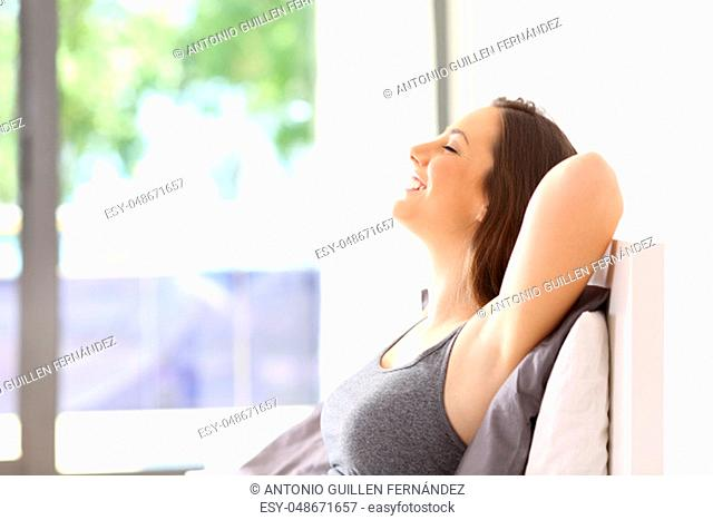 Side view portrait of a single happy woman relaxing sitting on the bed of an hotel room or home