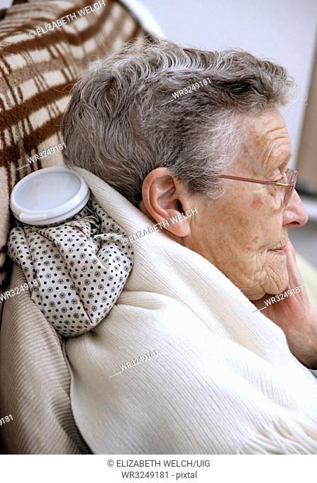 Elderly woman using a hot water bottle for neck and shoulder pain
