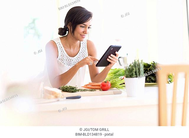 Hispanic woman cooking with digital tablet