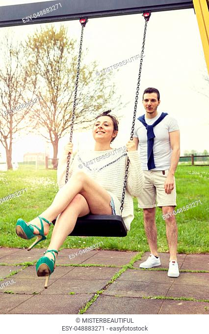 young man pushes her girlfriend on the swing outdoor in the park