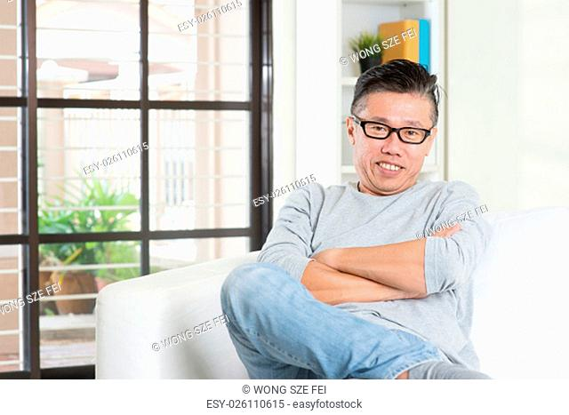 Portrait of happy mature 50s Asian man smiling and sitting at home. Senior Chinese male relaxed and seated on sofa indoor