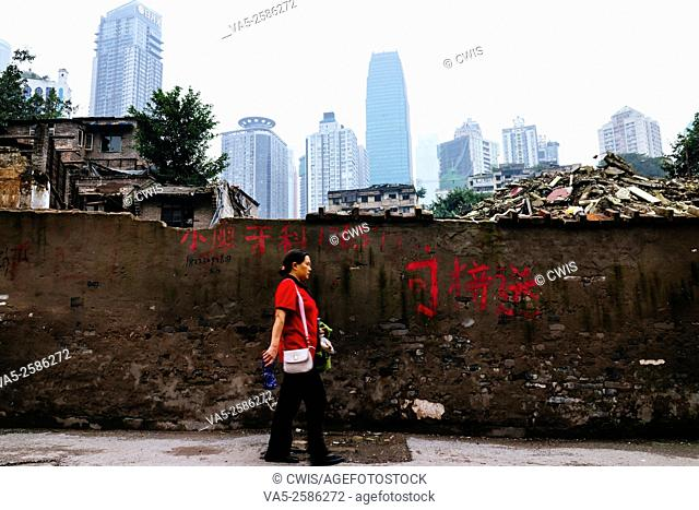 Chongqing, China - The view of the ruins of the famous old shanty town, Shibati, after demolition in the daytime, a local people walking by