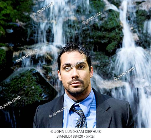 Hispanic businessman in front of waterfall