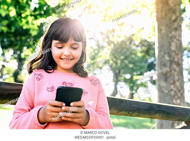 Smiling girl sending messages with her smartphone