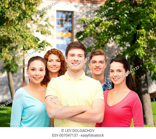 friendship, education, summer vacation and people concept - group of smiling teenagers standing over campus background