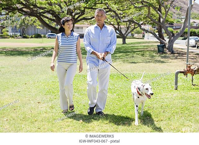 Husband and wife walking with dog