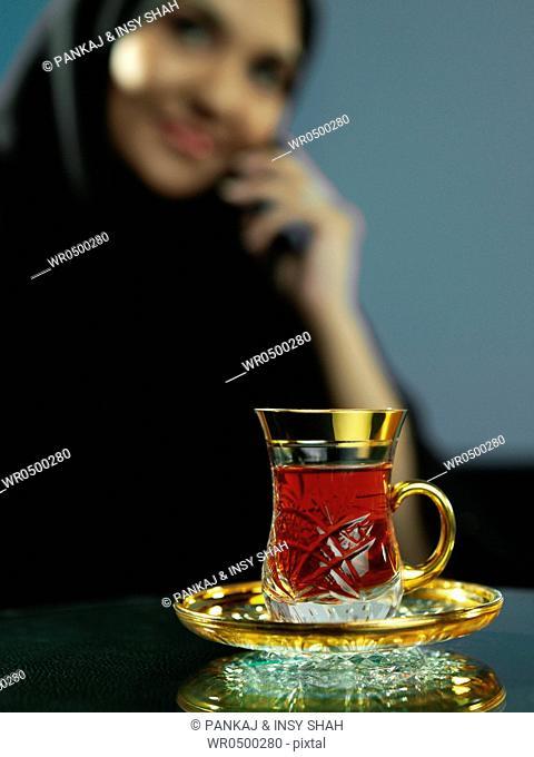 An Arab lady drinking tea