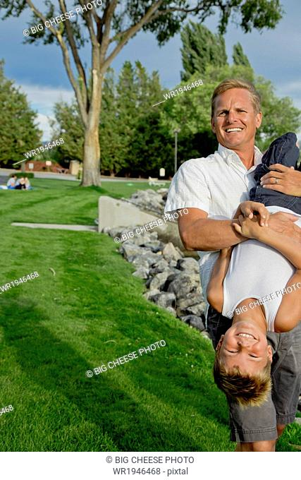Father holding his young son upside down