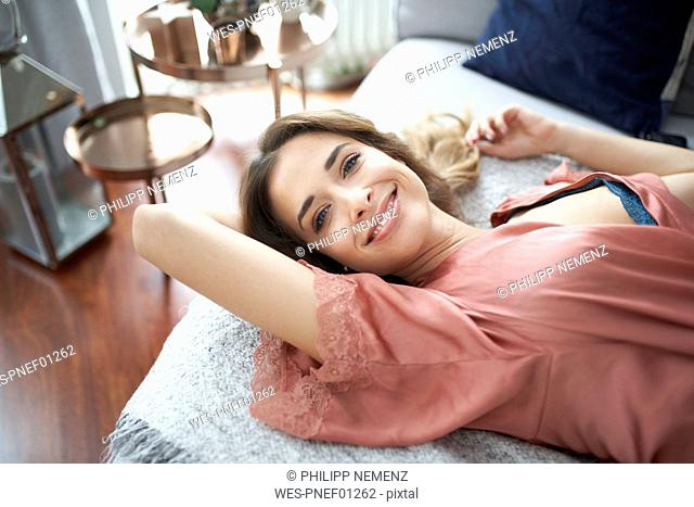 Portrait of smiling young woman in dressing gown lying in bed