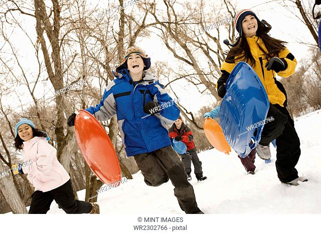 A group of children, boys and girls, running across the snow carrying sledges