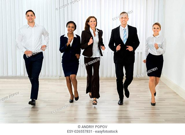 Group Of Professional Businesspeople Together Running In Office