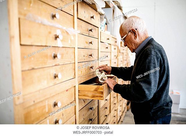 Senior man looking for decals for ceramics