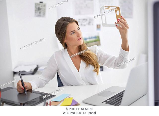 Young woman at desk in office holding model and using graphics tablet