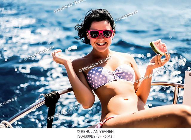 Woman in bikini enjoying sun and sea on boat