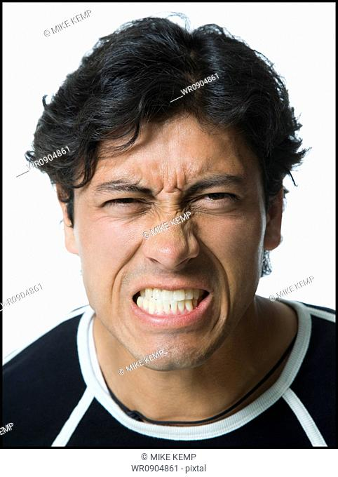 Portrait of a young man clenching his teeth