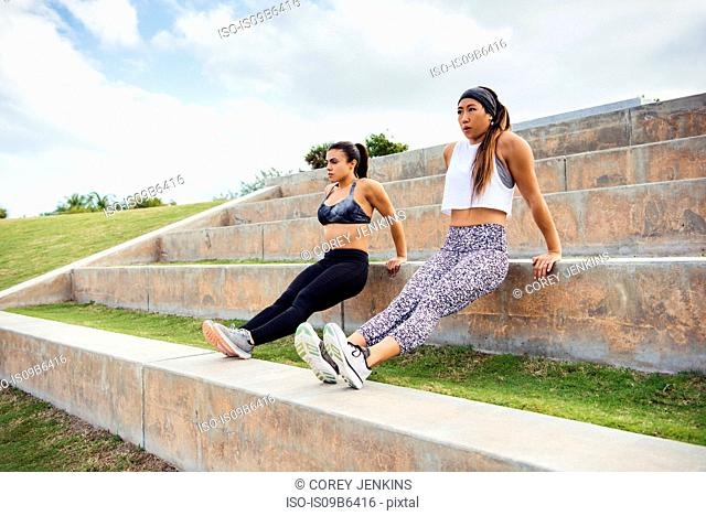Two young women exercising outdoors, doing push-ups on steps, South Point Park, Miami Beach, Florida, USA